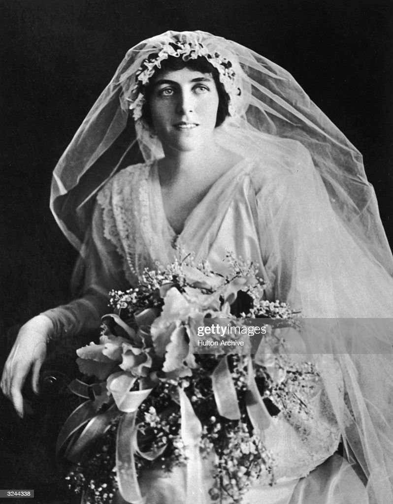 Portrait of Eleanor Wilson (1889 - 1967), youngest daughter of President Woodrow Wilson, wearing a wedding gown and holding a bouquet of flowers.