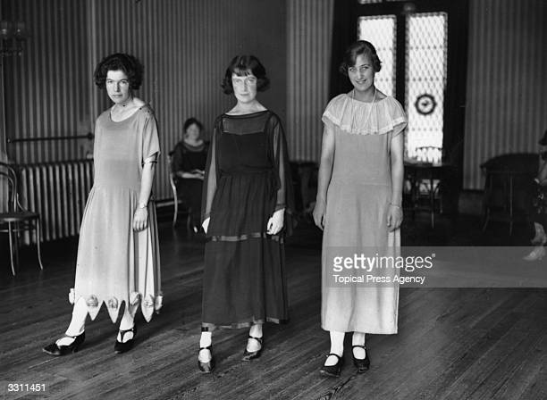 Three pupils demonstrating the correct and incorrect ways for a lady to walk at a deportment class