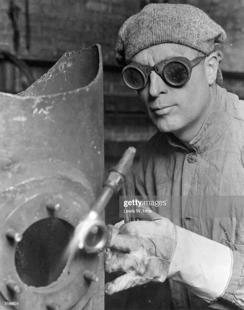A man welds a piece of metal machinery using an oxy-acetylin blow torch. He wears a cap, protective goggles and gloves.