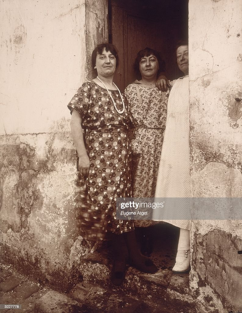 Full-length image of three middle-aged women standing in the doorway of a home located along the Rue Asseline in Paris, France. Photograph by French photographer Eugene Atget, titled 'Rue Asseline'.