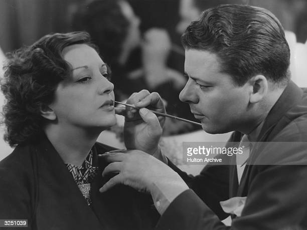 The makeup director of Twentieth Century Fox placing the finishing touches on the lips of American actress Estelle Taylor