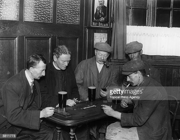 The Reverend E Scarlett enjoying beer and dominoes with some of his parishioners in their local pub in Chessington