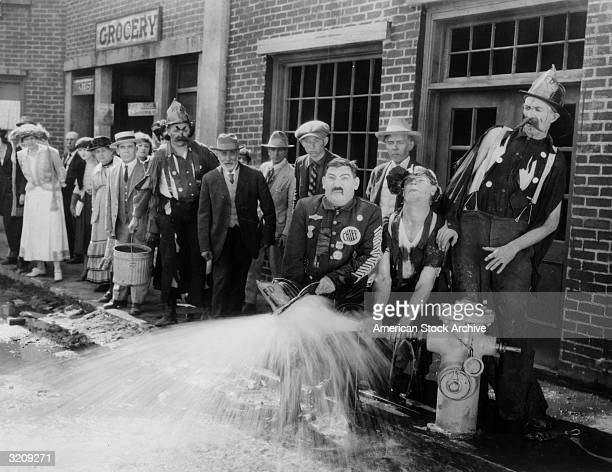 A crowd watches a fire chief and his crew attempting to control a spraying hydrant in a still from an unidentified slapstick film