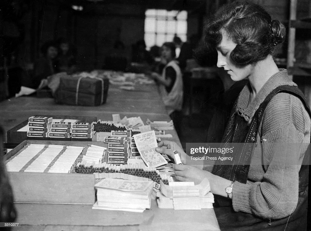 A girl putting cross-word puzzles into boxes of cigarettes, at a cigarette manufacturing factory.