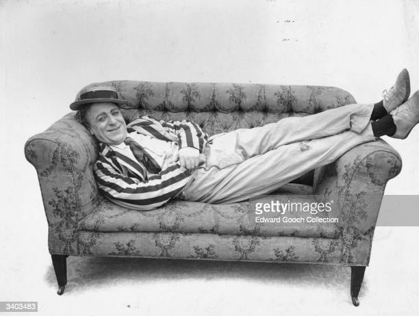 A man in a striped blazer and straw boater reclining on a couch