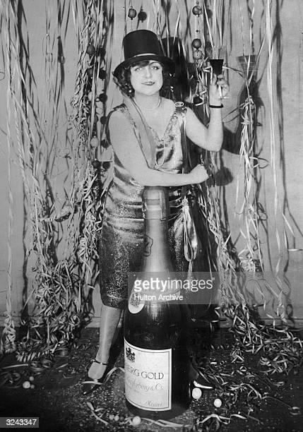A woman at a New Year's Eve party leans on an oversized bottle of champagne while making a toast Germany
