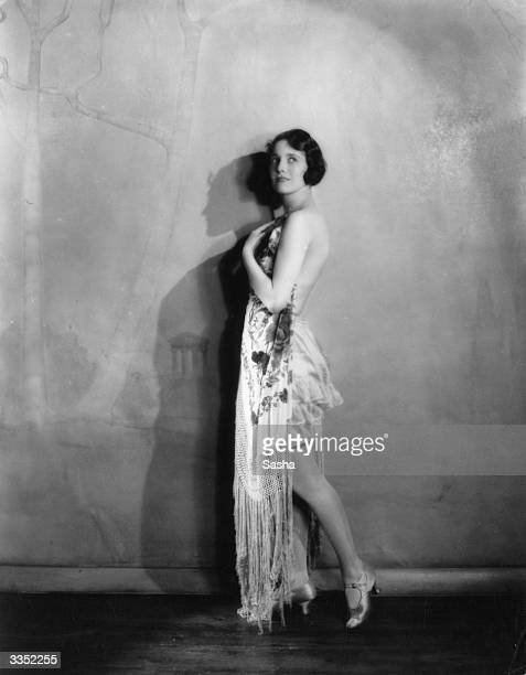 Actress Doris Bentley standing in a studio wearing bloomers and draped in a shawl
