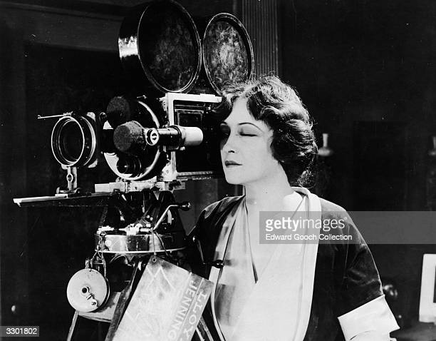 American actress Pauline Frederick takes a look through the camera on the set of the film 'The Woman In Room Thirteen'
