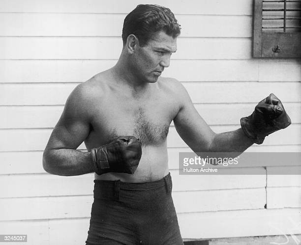 American boxer Jack Dempsey poses outdoors in a fighting stance He wears boxing trunks and gloves