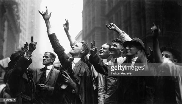 Curb Market traders gesture with their hands to trade stocks on Wall Street New York City The Curb Market was for stocks not listed on the New York...