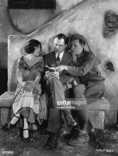 French actress Renee Adoree and her leading man John Gilbert sitting with director King Vidor during the filming of his World War I drama 'The Big...