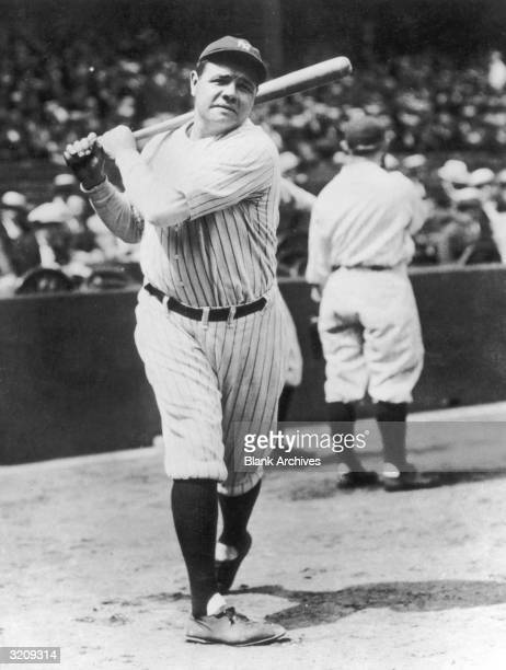 Fulllength image of American baseball player Babe Ruth taking a practice swing with a baseball bat on the field in a stadium