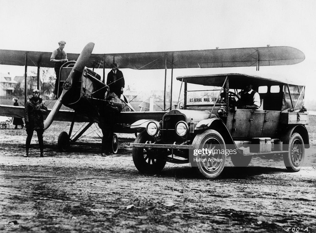 Full-length view of a US Aerial Mail Service biplane, a pilot, postal workers and a postal automobile on an airfield in Cleveland, Ohio. This was the inagural flight for the service between Cleveland and Chicago.