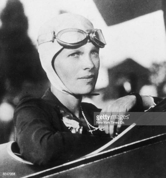 Headshot portrait of American aviator Amelia Earhart sitting in the cockpit of her plane