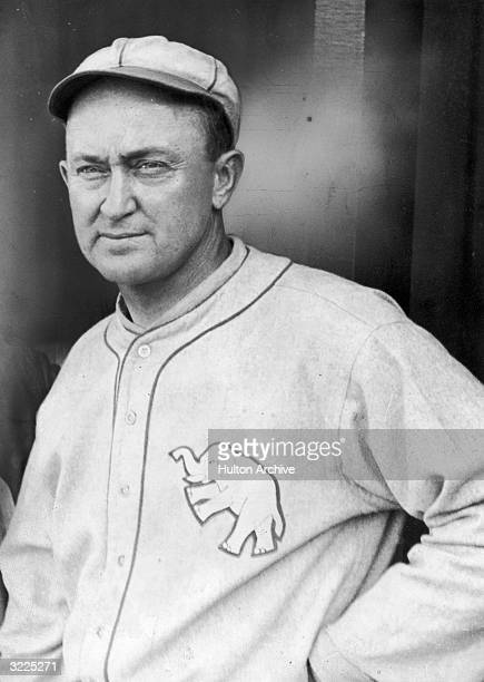 Portrait of American baseball player Ty Cobb wearing his Philadelphia Athletics cap and shirt 1920s He has one hand on his hip