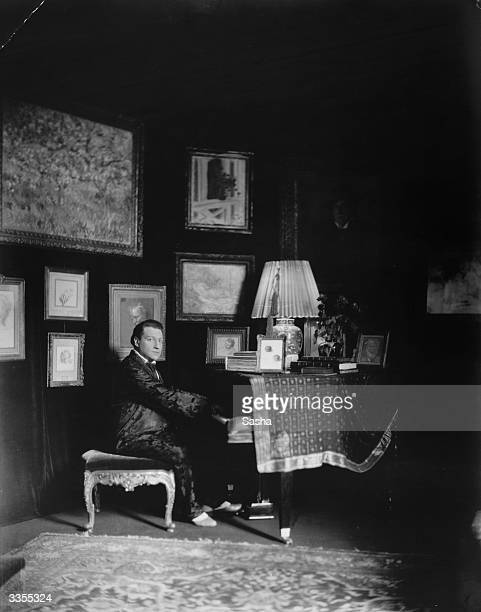 Russian born French actor and film director Sacha Guitry at his piano
