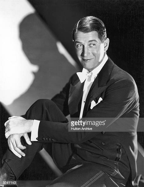 Studio portrait of French cabaret singer and actor Maurice Chevalier sitting and holding his knee towards his chest He is wearing coattails and a...