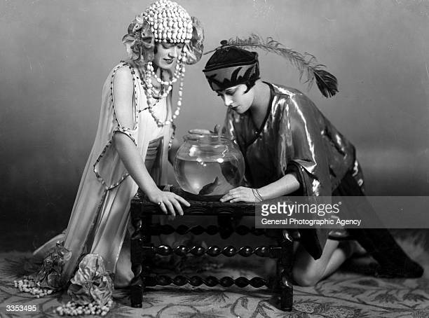 Two actresses looking at fish in a bowl during a performance of Aladdin