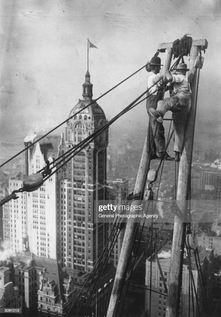 Two workers high above lower Manhattan, during the construction of a skyscraper. The Singer Building is in the background.