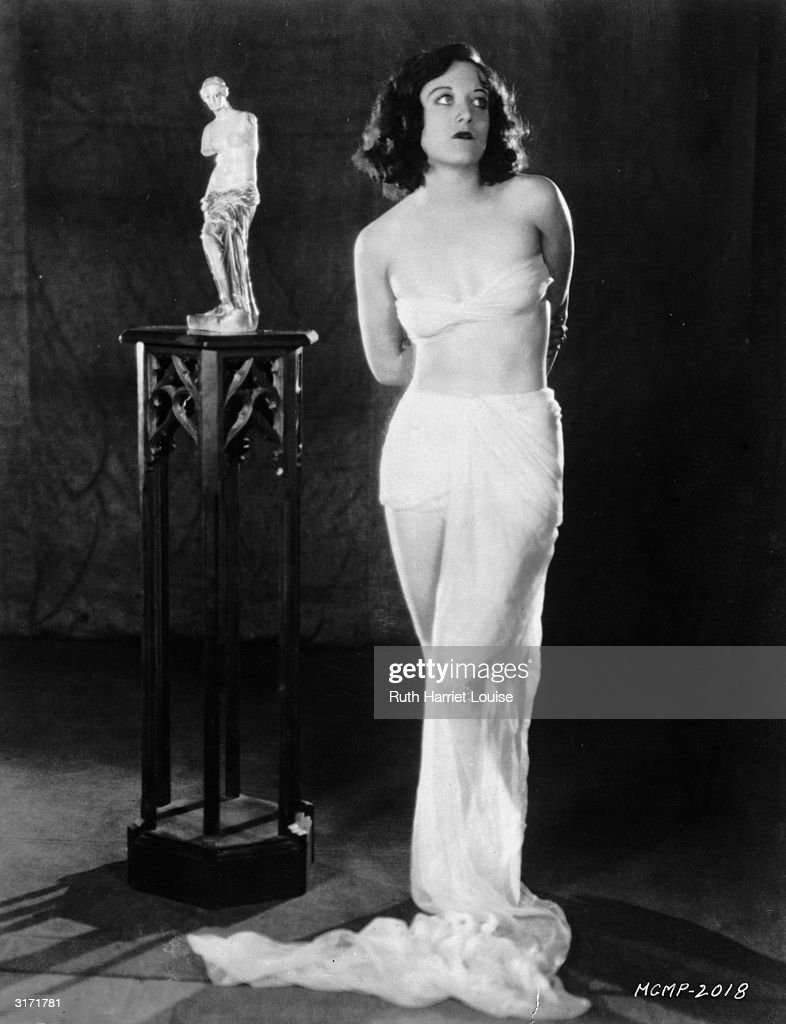With her arms held behind her back and in bra and draperies film star Joan Crawford poses beside a small statue of the Venus de Milo