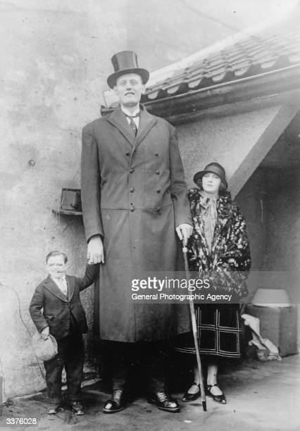 An immensely tall man standing next to a woman of average height and a midget