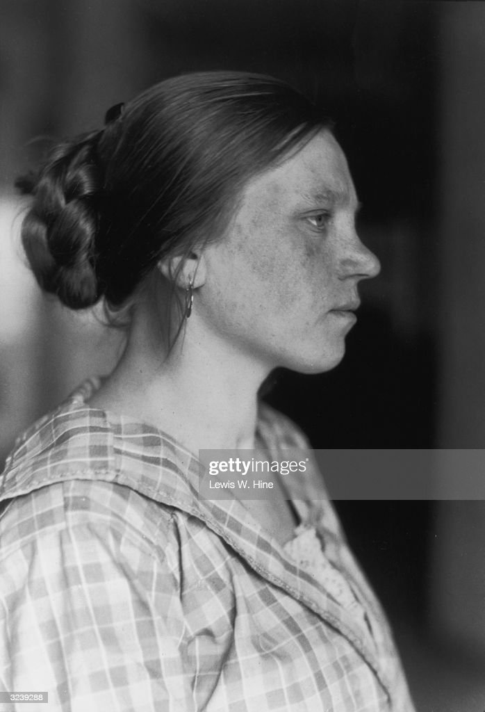 Profile portrait of an Eastern European immigrant woman, wearing a checkered dress, with her hair pulled back in a bun, Ellis Island, New York City.