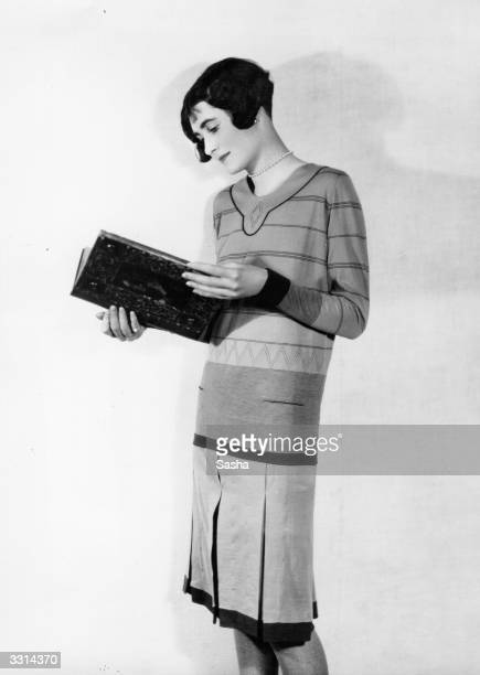 A woman modelling a dress while reading a book