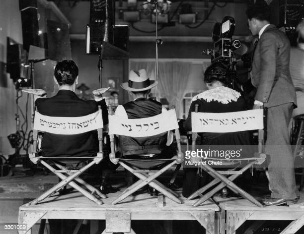 Actors Vera Gordon and John Gilbert and director William Nigh sitting in chairs which have been inscribed with their names in Yiddish at the...