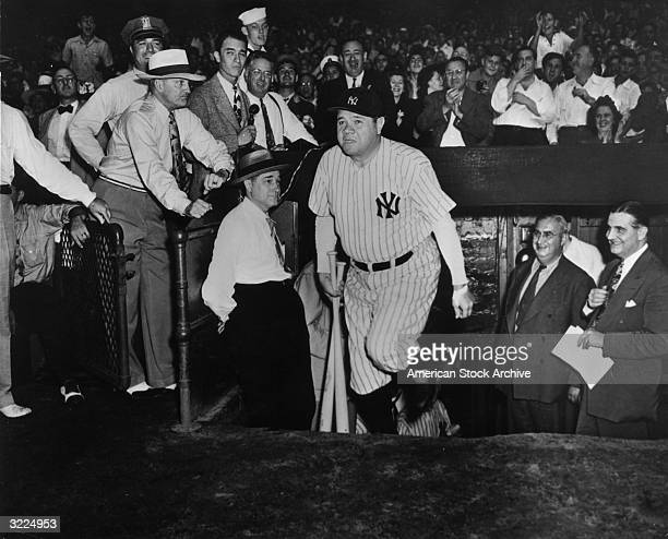 American baseball player Babe Ruth walking out of the Yankees' dugout as fans applaud his appearance