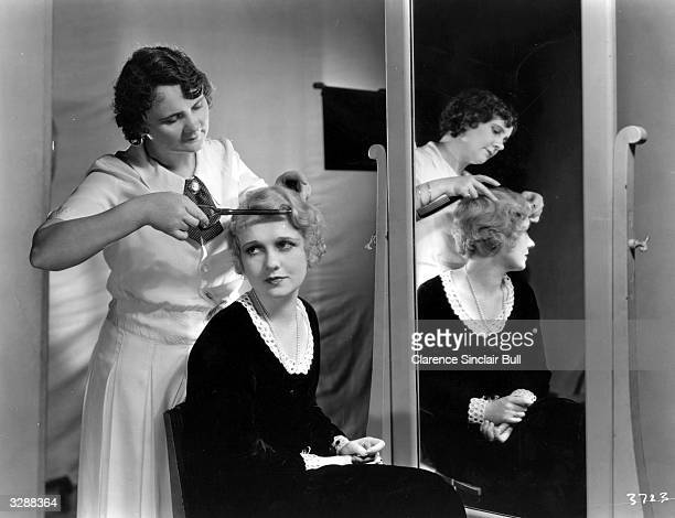 Anita Page the film actress is pictured with her new hairstyle especially created by Edith Rubner who is applying the finishing touchesTo suit her...