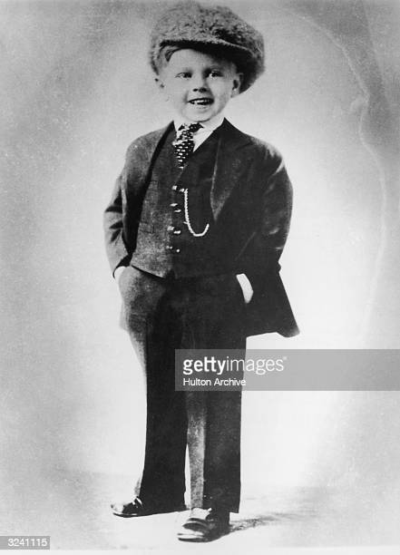 Fulllength portrait of American actor Mickey Rooney as a young boy wearing a threepiece suit tie and large cap Rooney is smiling and has his hands in...