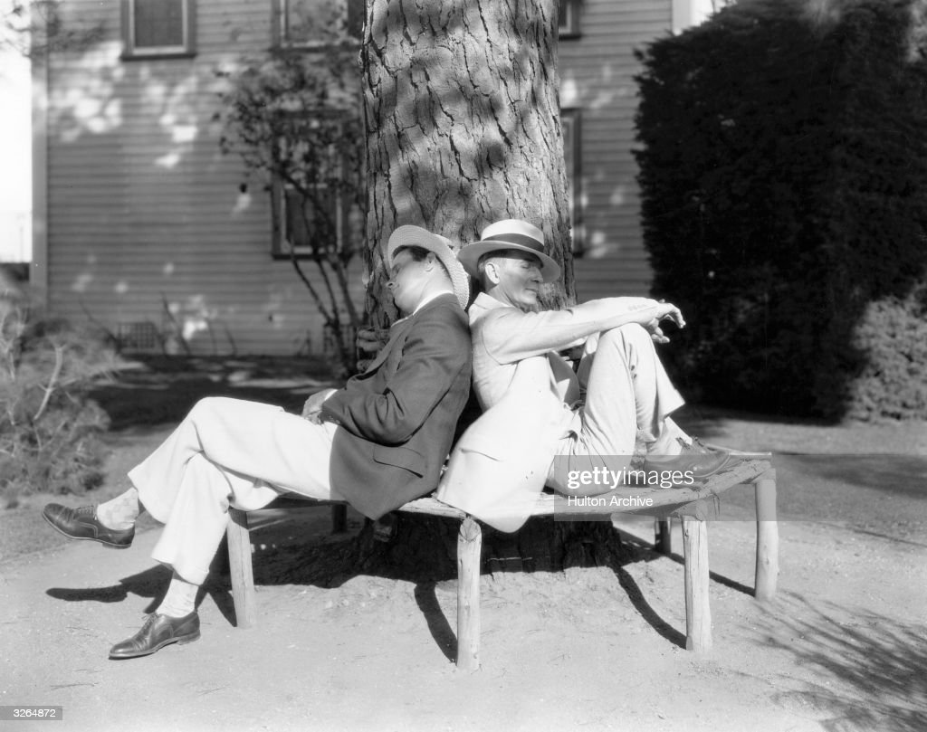 Tay Garnett (1894 - 1977), the Hollywood film director and screenwriter, with Hal Conklin snoozing in the garden. They were working on 'The Spieler' for Pathe.