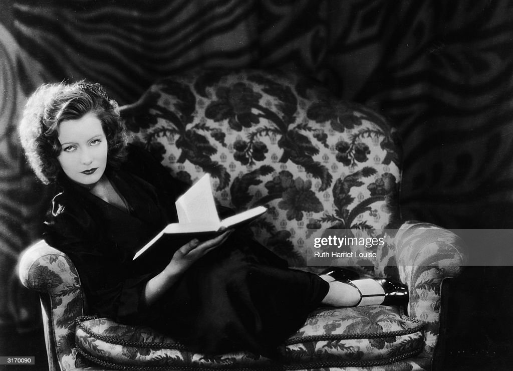 Swedish born American actress Greta Garbo (1905 - 1990) curled up on a chair with a book.