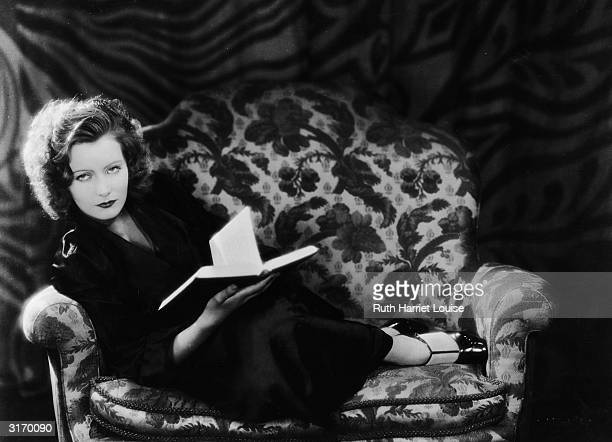 Swedish born American actress Greta Garbo curled up on a chair with a book