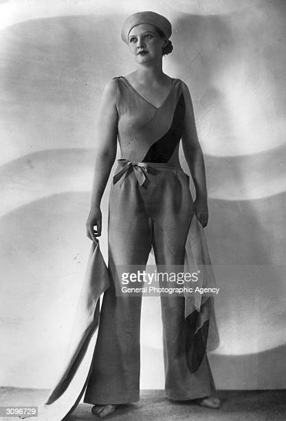 A woman modelling a pair of loose summer trousers decorated with a bow a diagonally striped vest top and a sailor hat