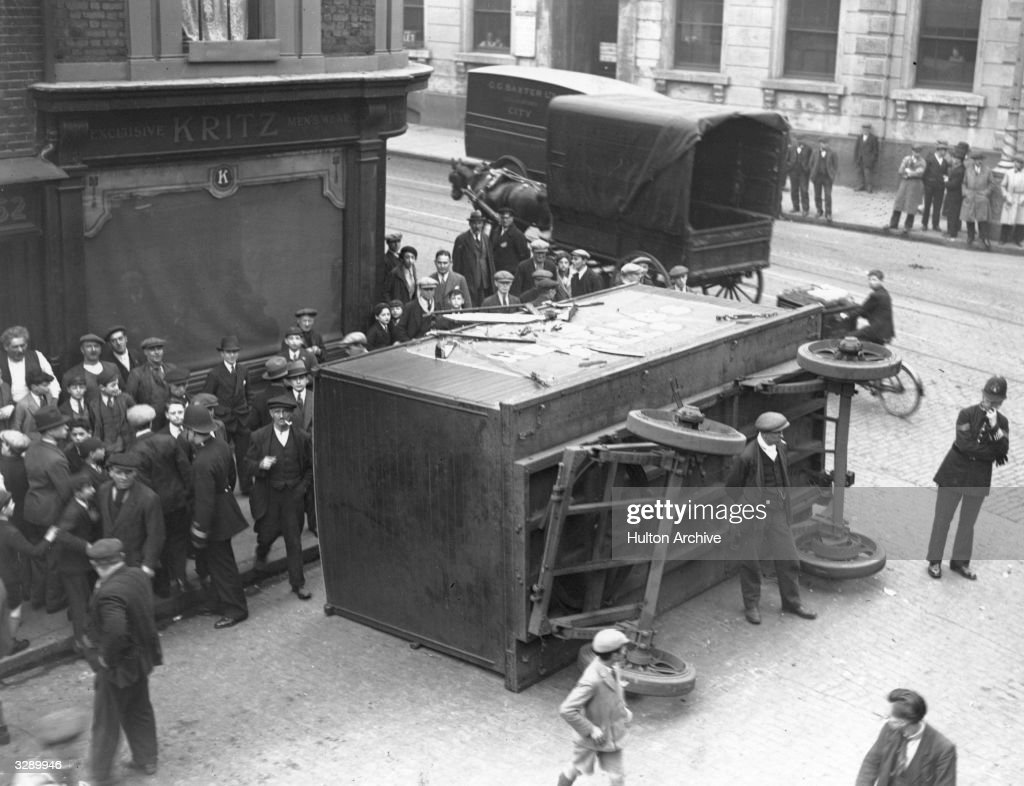 A crowd gathers to see the lorry and tram crash in London's Whitechapel which left the lorry on its side