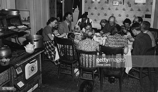 A family sitting round a large table for an old fashioned Christmas dinner