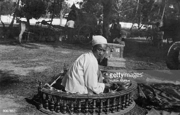 A gamelan being played in Burma The gamelan consists of a circle of small drums which have a boss in the centre and are played by a man sitting in...