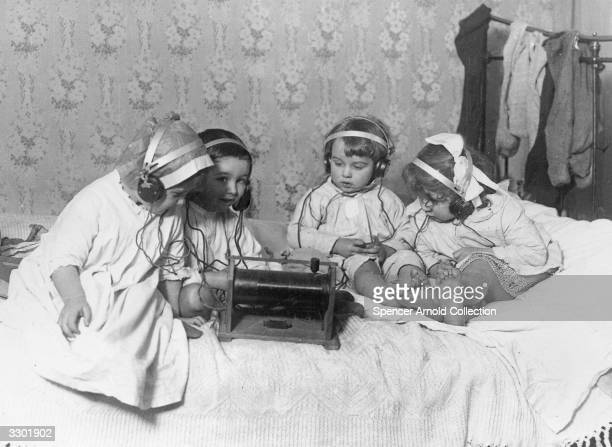 A group of young children sitting on a bed listening to the radio on headphones