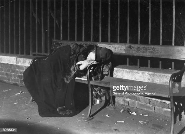 A homeless woman sleeping under her coat on a park bench