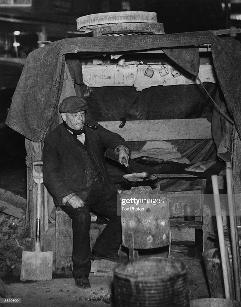 A nightwatchman keeping warm and cooking his supper on a brazier