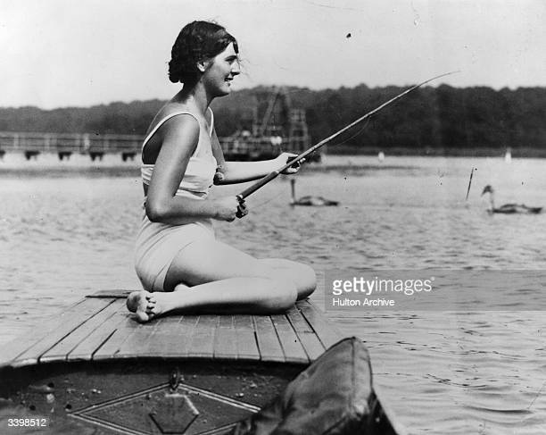 A woman fishing in a British river from a boat