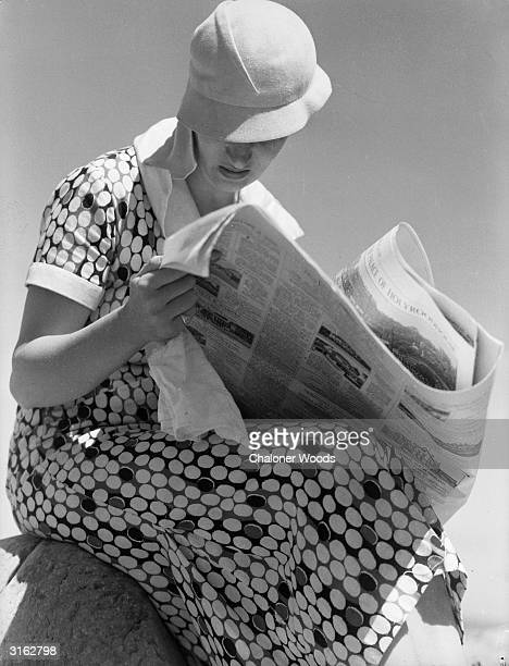 A woman in a spotted dress and a jaunty cap sits down to read the newspaper