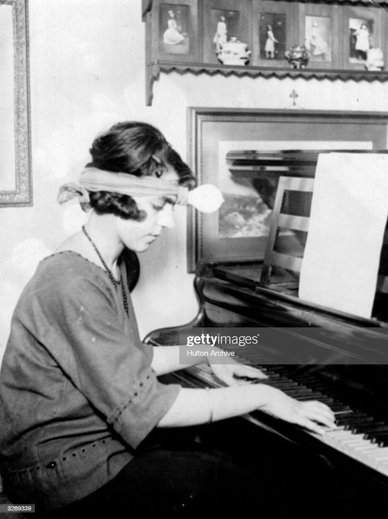 A woman playing the piano by the light of a bulb tied to her forehead.