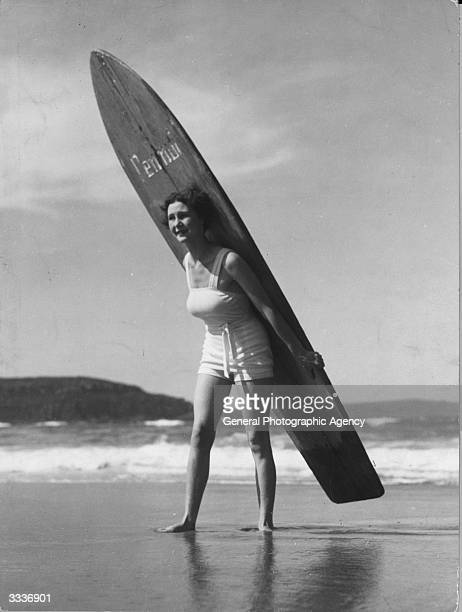 A young woman carrying a surf board on her back