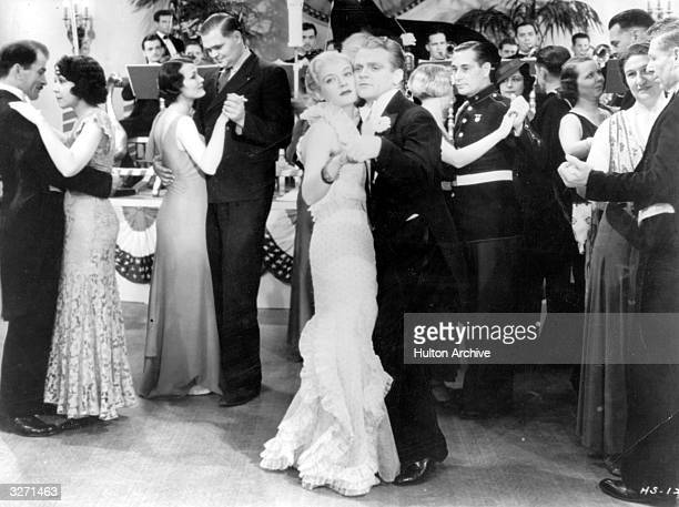 American actor James Cagney dances with a young lady in a scene from an unknown film