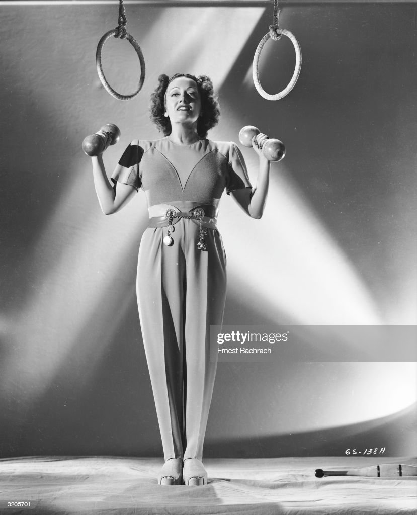 American actress Gloria Swanson (1899 - 1983) lifts a pair of small weights while a set of rings hang over her head.