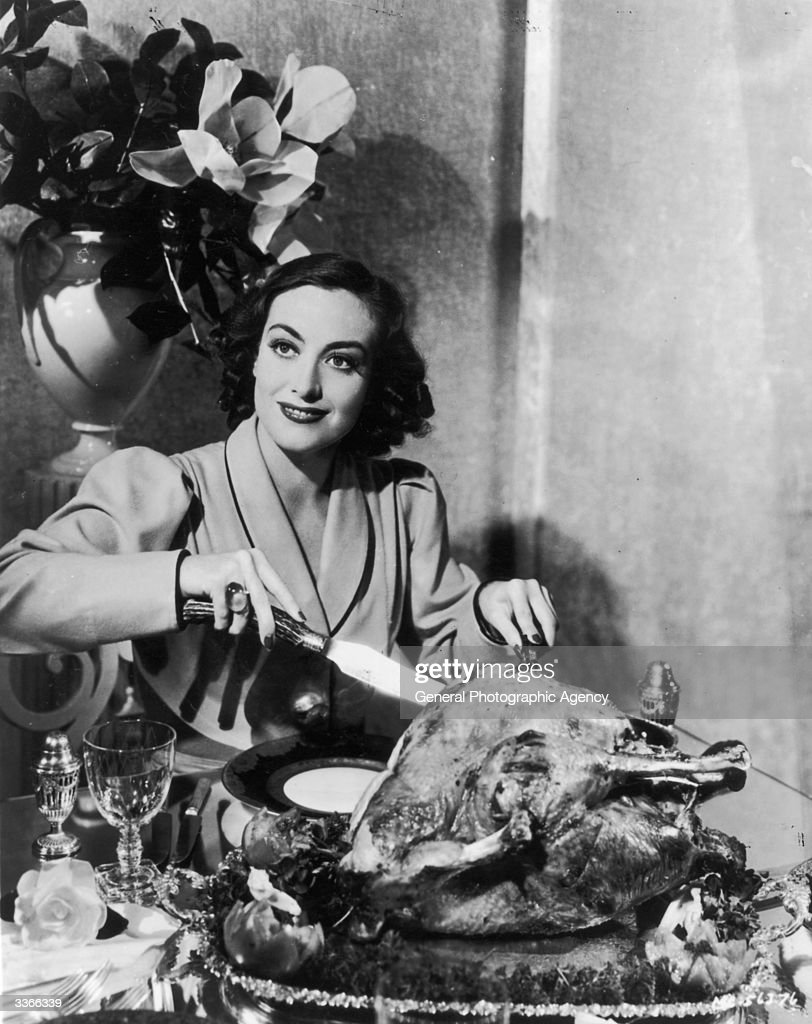 American actress Joan Crawford carving a huge Thanksgiving turkey for a publicity shot Oddly movie stars were often requested to strike this pose by...