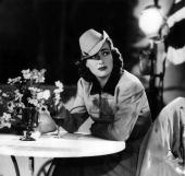 American film actress Joan Crawford sitting at a table
