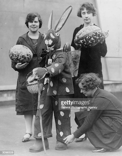 An Easter bunny carries easter eggs in a basket on his back while one woman adjusts his turnups and two others carry large easter eggs